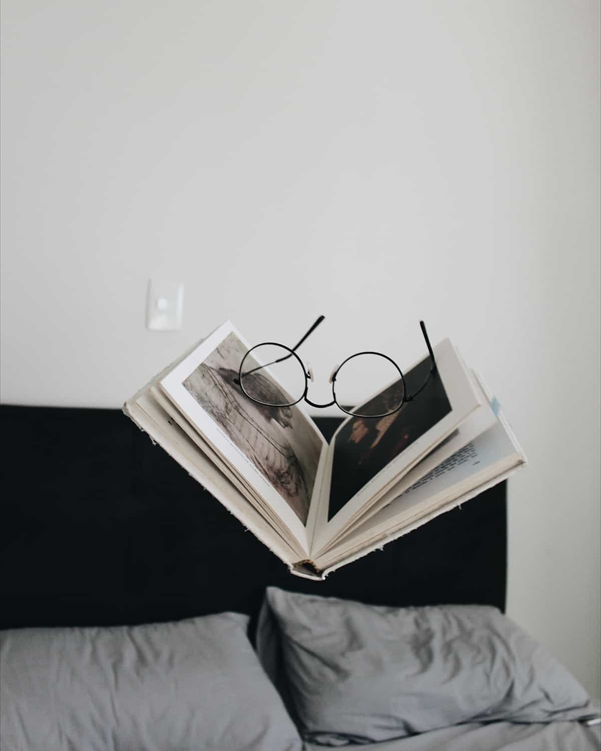 book and glasses over bed