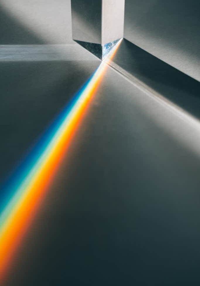 Bright shaft of sunlight passes through a glass prism creating a rainbow light effect